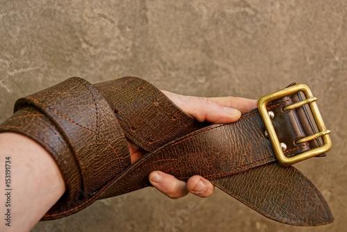 Fotografía  Коричневый ремень намотанный на руку на фоне серой бетонной стены