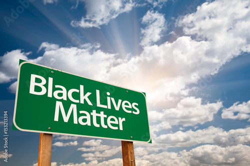 Photo Black Lives Matter Green Road Sign with Dramatic Clouds and Sky