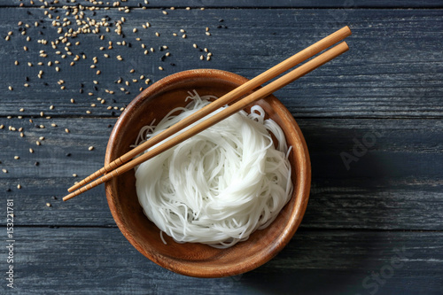 Bowl with rice noodles on wooden table