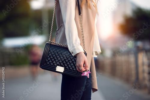 Plakat Zamyka up elegancka żeńska czarna rzemienna torba outdoors. Modna i luksusowa kobieca torba w stylu.