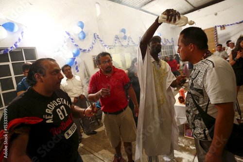 A voodoo priest pours perfume on the head of a man during a
