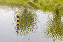 Water Level Pole Indicating Water Depth Of Natural Lake In Summer.