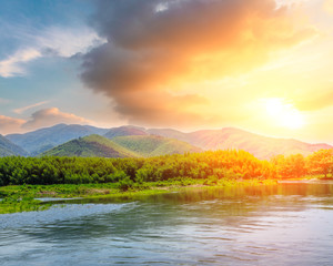 River and green mountains landscape at sunset