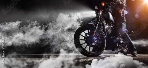 Tuinposter Fiets Close-up of high power motorcycle chopper with man rider at night