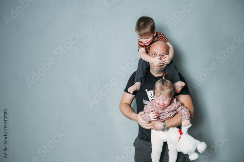 Obraz stressed young dad with two small children in his arms - fototapety do salonu