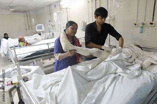 Medical assistants treat a man for fire burns at Dhaka Medical