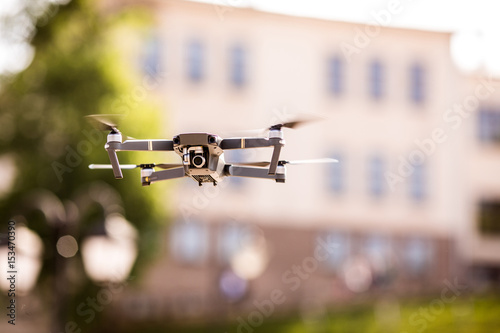 Valokuva  drone quad copter with high resolution digital camera flying hovering in the blu