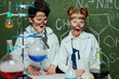little kids in white coats with chalkboard behind in science laboratory, scientists kids team concept