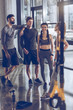 group of athletic young people in sportswear standing and resting at the gym, group fitness concept