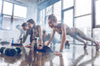 canvas print picture - group of athletic young people in sportswear doing push ups or plank at the gym, group fitness concept