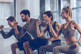 group of athletic young people in sportswear doing lunge exercise at the gym, aerobic fitness concept