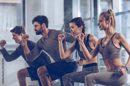 Slika na platnu group of athletic young people in sportswear doing lunge exercise at the gym, ae