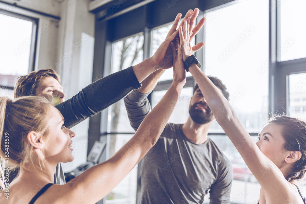 Fototapeta Happy young athletic people in sportswear giving high five in gym