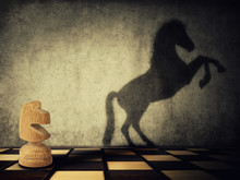 Magical Transformation As A Wooden Knight Chess Piece Casting A Shadow Of A Wild Horse On Two Legs On The Wall. Symbol Of Business Aspirations, Freedom And Leadership Concept.