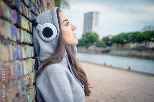 Young and sad woman listening music from her headphones outdoor