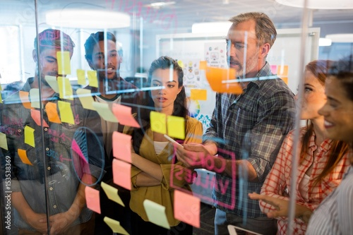 Cuadros en Lienzo  Creative business team looking at sticky notes on glass window
