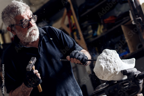 Fotografia Senior sculptor working on his marble sculpture in his workshop with hammer and chisel