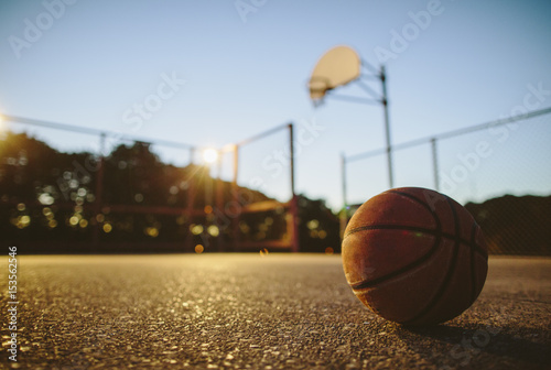 Close-up of basketball on ground in court during sunset