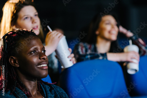 Fotografie, Tablou  Black woman enjoying a sweet romantic comedy at the movies