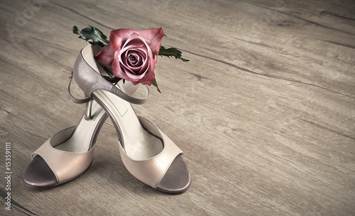 Fotografie, Obraz  Argentine tango shoes and a rose on a wooden floor, space