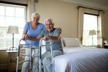 Senior Woman Helping Man To Wa...