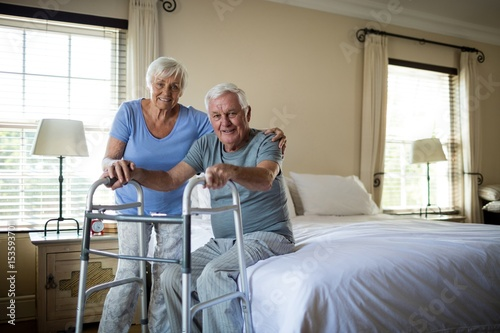 Senior woman helping man to walk with a walker Fototapet