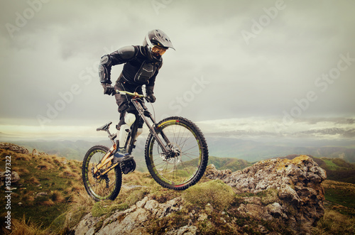 Photo  Ryder in full protective equipment on the mtb bike climbs on a rock against the