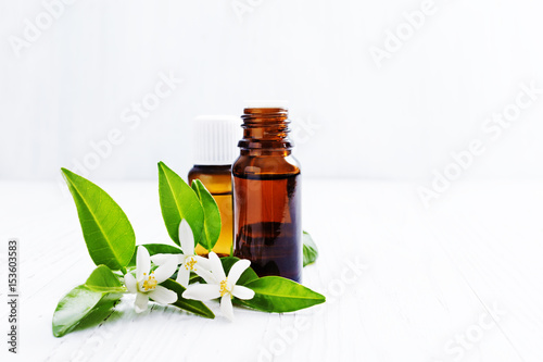 Fototapeta Neroli (Citrus aurantium) essential oil in a brown glass bottle with fresh white  flowers on ligth background. Selective focus. obraz
