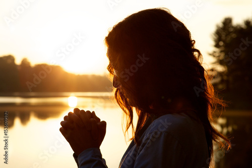 Woman in prayer at sunrise by lake Fototapeta
