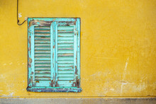 Yellow Wall With Old Window Shutters