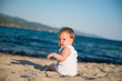 Adorable baby girl on sunny sand beach