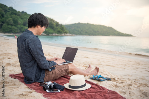 Fotografia Young Asian man working with laptop computer on tropical beach, digital nomad li