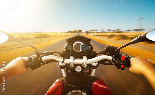 Biker driving a motorcycle rides along the country road , morning scene Wallpaper Mural