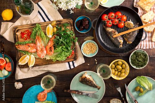 Foto op Plexiglas Japan Dinner table with shrimp, fish grilled, salad, snacks and wine