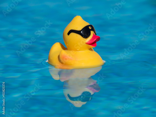 Photo  Yellow rubber duck with black sunglasses floating on a beautiful blue swimming pool