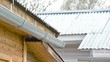 rain and snow falling on the metal roofs of houses in the countryside in spring, dripping on the pipe drainage in Russia