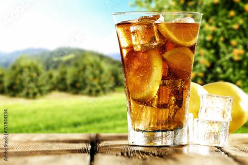 mrozona-herbata-w-kubku-pelnym-kostek-lodu-na-tle-slonecznej-polany