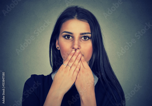 Fotografija brunette woman covers her mouth with hands