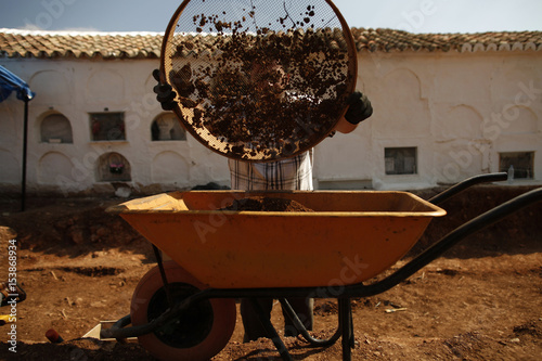 A Technical Worker Uses Sift To Find Human Bone Fragments In Mass Grave