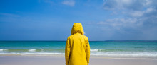 A Rear View Of A Lone Woman Wearing A Bright Yellow Hooded Jacket And Facing Away From The Camera Towards The Ocean On A Deserted, Sandy Beach.