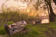 A Misty Summer Morning On The River Or Lake.  Old Rough Wooden Fishing Boats On Green Grass And Water, Sunrise, Fog. Lonely Calm Mood Nature Concept.  Copy Space, Horizontal Wallpaper Or Background.
