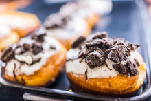 Vanilla White Iced Donuts With Chocolate Sandwich Cookies Crumbled On Top