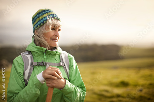 Confident mature woman hiking in the countryside.