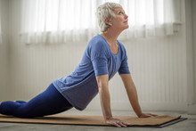 Mature Woman Practising The Cobra Pose During A Yoga Practise.