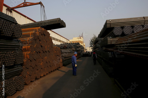 A worker stands next to a pile of steel pipes at the yard of