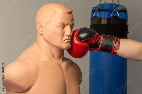 Photo  Caucasian boxer wearing red boxing gloves punching straight on a dummy mannequin