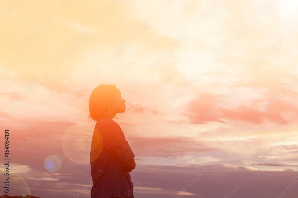 Fototapeta Silhouette of woman praying over beautiful sky background
