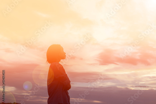 Fotografie, Tablou  Silhouette of woman praying over beautiful sky background
