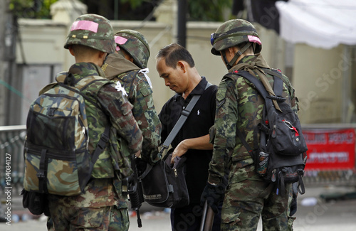 Thai army soldiers check the bag of a man at a road blockade