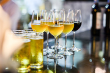 Close Up Of A Glass Of Beer, Wine And Champagne In A Bar. Many Glasses Of Different Alcohol Drink In A Row On Bar Counter